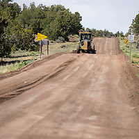 060613       Brian Leddy<br /> A road grader works on New Mexico Highway 400 Wednesday afternoon. The road, which starts at Interstate 40 and ends at McGaffey, is being repaved in the section of the Cibola National Forest.