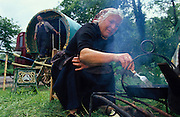 Breakfast fire. Romany gypsies, Leslie and Edna traveling with a traditional bowtop wagon in the English countryside...English Romany Gypsies traditionally traveled the country roads camping nearby towns and villages, choosing the grassy roadside banks, where they tethered their horses, or in farmer's fields, when they were allowed. Travelling in bowtop wagons drawn by horses, and before that with tents, sometimes with horse drawn carts or just by foot. Often they worked as casual agricultural labourers, doing the seasons work. They also could earn their living in different ways, sometimes selling their wares, brass, tin, wood and cloth, such as embroidered cloths or lace, telling fortunes, music and dancing, and through crafts skills in basket making, plaiting chair bases, sharpening knives,  They would make fires from old wood, cleaning up after them when they moved on. There were several horse fairs, notably Appleby in Cumbria and Stow-on-Wold in the Cotswolds where they trade and sell horses, some traditions which keep to this day.