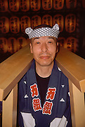 A portrait of a mikoshi or portable shrine supporter in front of a large display of yellow paper lanterns, each carrying the name of a fallen serviceman, at the Mitama matsuri or festival of remembrance for Japanese war dead Yasukuni shrine, Tokyo, Japan, Monday, July 16th 2007
