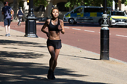© Licensed to London News Pictures. 16/06/2021. London, UK. A woman jogs during sunny weather near St James's Park in Central London. Temperatures are expected to rise with highs of 30 degrees forecasted for parts of London and South East England today . Photo credit: George Cracknell Wright/LNP