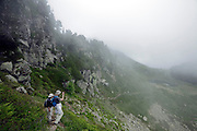 two hikers with low hanging clouds moving in France Ariege