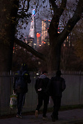 Three men walk along park railings where  the Shard and skyscrapers in the City of London's financial district are seen through autumn branches in Ruskin Park, on 4th November 2020, in London, England,