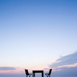 Table and chairs on a beach at dawn.