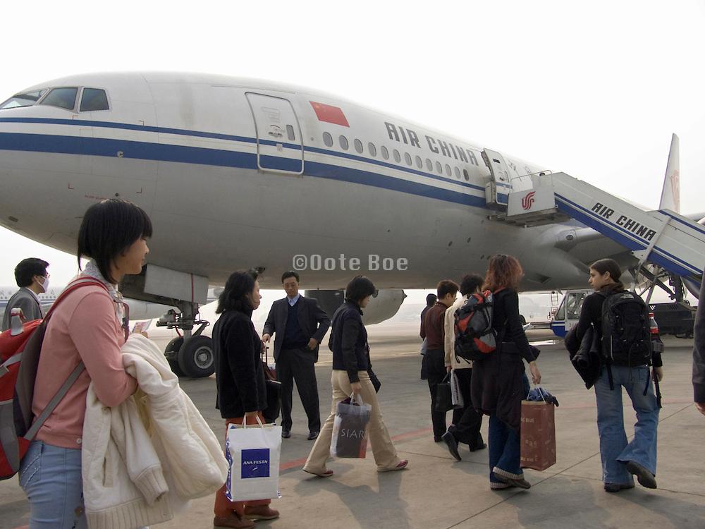 people walking to the waiting airplane China Beijing