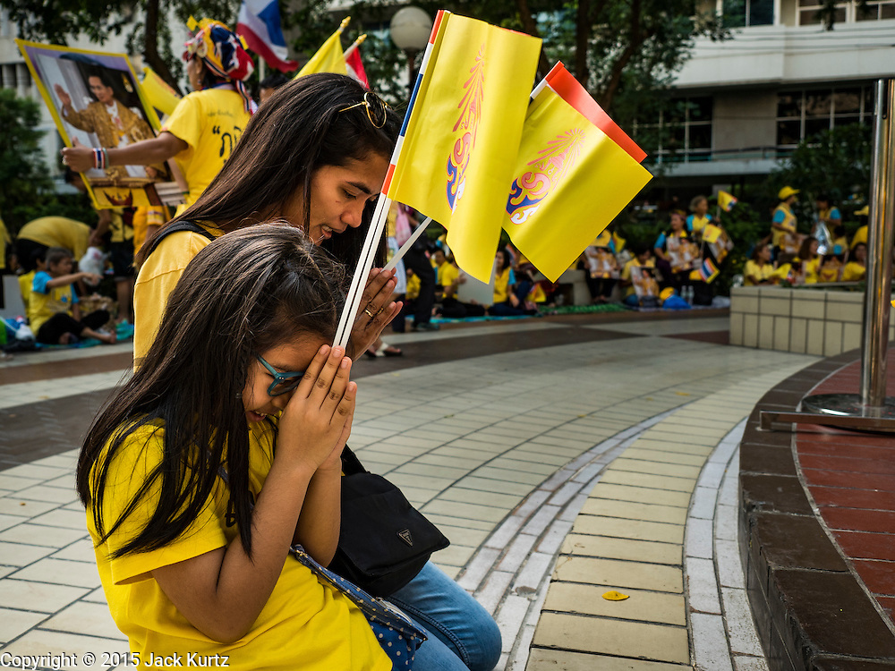 05 DECEMBER 2015 - BANGKOK, THAILAND:  A mother and daughter pray for the King in the plaza at Siriraj Hospital on the 88th birthday of Bhumibol Adulyadej, the King of Thailand. Hundreds of people crowded into the plaza hoping to catch a glimpse of the revered Monarch. The King has lived at Siriraj Hospital off and on for more than four years.    PHOTO BY JACK KURTZ