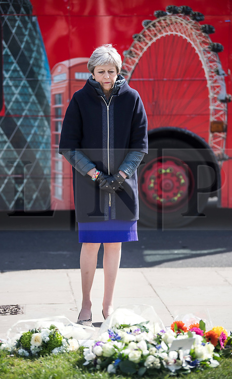© Licensed to London News Pictures. 22/03/2018. London, UK. British Prime Minister THERESA AMY places a floral tribute at Parliament Square, outside the Houses of Parliament in Westminster, London on the one year anniversary of the Westminster Bridge Terror attack in which lone terrorist killed 5 people and injured several more, in an attack using a car and a knife. The attacker, 52-year-old Briton Khalid Masood, managed to gain entry to the grounds of the Houses of Parliament and killed police officer Keith Palmer. Photo credit: Ben Cawthra/LNP
