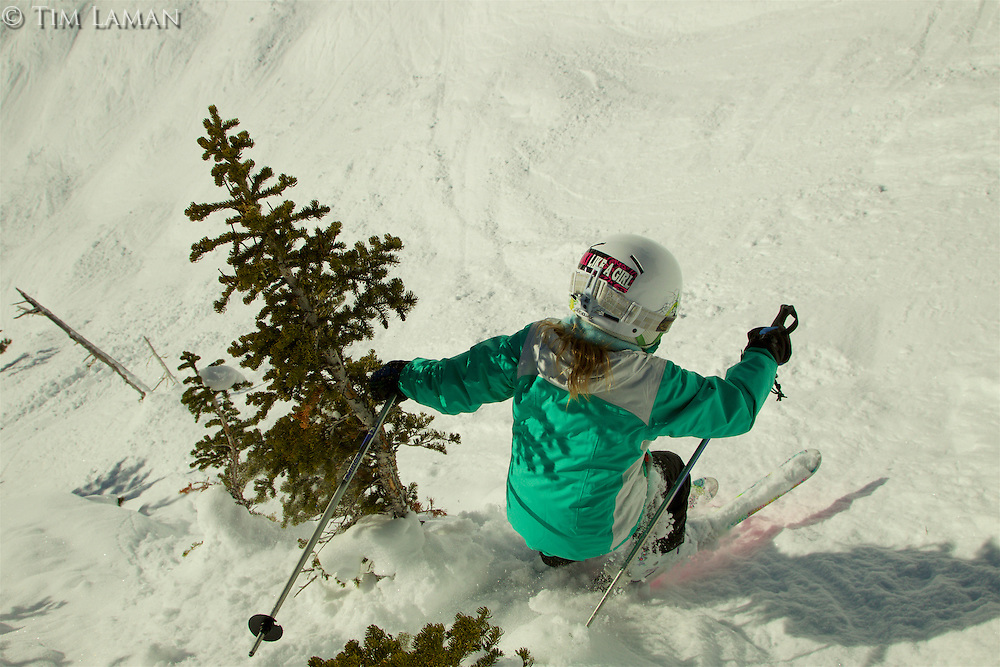"""Jessica Laman (age 9) jumps into a steep ravine in Jackson Hole, Wyoming.<br />Sticker """"Ski Like a Girl"""" on her helmet."""