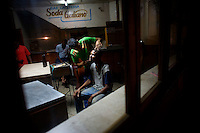 Cuban gets beard trimmed in barbershop at night.