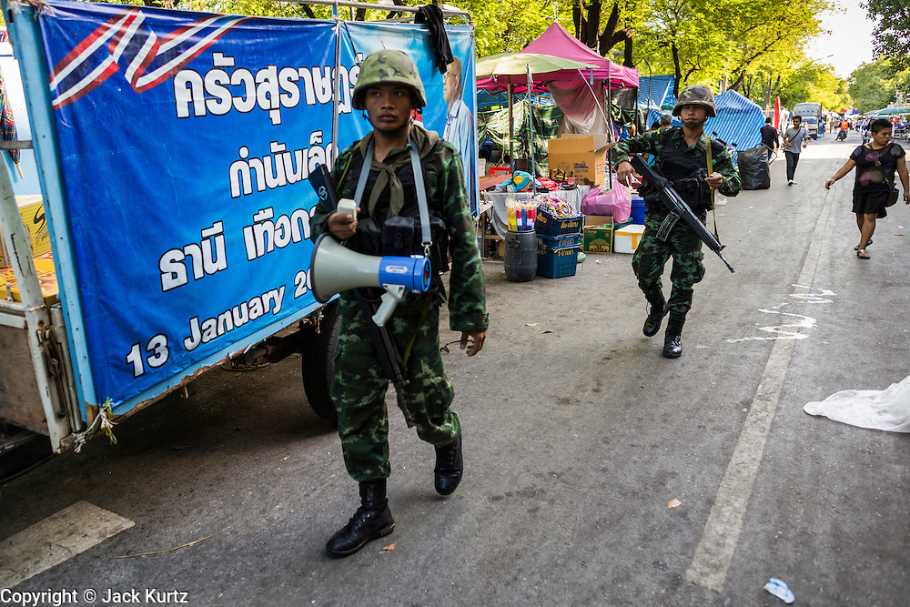 23 MAY 2014 - BANGKOK, THAILAND: Thai soldiers on a foot patrol through the anti-government protest area Friday morning. The soldier was using the bullhorn to make announcements about the coup and to tell protestors to go home. The Thai military seized power in a coup Thursday evening. They suspended the constitution and ended civilian rule. This is the 2nd coup in Thailand since 2006 and at least the 12th since 1932. The army has ordered both anti-government protestors in Bangkok and pro-government protestors in the suburbs to go home and arrested leaders of both groups.    PHOTO BY JACK KURTZ