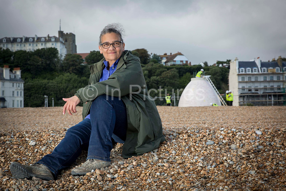Turner Prize nominated Lubaina Himid MBE during the construction of her Jelly Mould Pavilion on Folkestone's sea front as part of the 2017 Folkestone Triennial. Folkestone, Kent. Lubaina Himid created a Jelly Mould Pavilion on Folkestone's sea front, on the former 'Rotunda' site of the town's fun fair, Lido and amusement park where the sugar of candy floss and toffee apples fuelled summer visitors. The pavilion's colourful decoration in the artist's signature patterning will serve as a reminder of the lost amusement park, as well as providing a beautiful shelter at the edge of the town to rest, look out to sea, and think about the role of sugar in Britain's history. Folkestone, Kent.