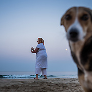 The moon is still in the sky and a local dog looks on as a woman practices Tai Chi early morning on Agonda beach in south Goa.