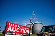 """06 AUGUST 2020 - FAIRFIELD, IOWA: A sign announcing the retirement auction on the Adam Farm near Fairfield. Gary Adam, 72 years old, has been farming in the Fairfield area since 1971. He decided to retire this year because he wants to travel and because it's so difficult to make money in farming this year. He said he wants to """"shed the risk and responsibility. If things were super good, like they were 2006-2012, I might stay in it, but they're not."""" An increasing number of farmers in the Midwest are retiring this year as it becomes harder to make money on crops. In addition to low prices, Iowa farmers are being hit with a drought this year, with well below average rain over most of the state. Because of the COVID-19 pandemic, the auction on Adam's farm was one of the first live in person auctions since winter. Most auctions are now done on line.    PHOTO BY JACK KURTZ"""