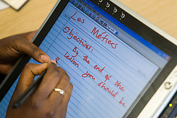 Teacher using tablet pc to plan the objectives of a Secondary School lesson,