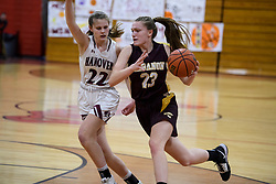 Lebanon senior Rebecca Wright navigates around Hanover sophomore Melissa Whitmore  in the NHIAA Division II semi-final game at Pinterton Academy in Derry on Wednesday, March 11, 2020.  (Alan MacRae/Valley News)