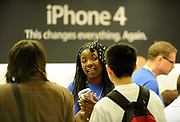 An Apple store employee talks to customers who are buying the new Apple iphone 4 in the Apple store in Regent street, central London