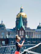 26 APRIL 2020 - DES MOINES, IOWA: A woman takes a picture from a bridge over the Des Moines River in downtown Des Moines. Capitol Hill Lutheran Church and the Iowa State Capitol are behind her. On Saturday, 25 April, there were 5,092 confirmed cases of COVID-19 in Iowa (an increase of 647 since Friday, April 24) and 112 deaths in Iowa caused by COVID-19.          PHOTO BY JACK KURTZ