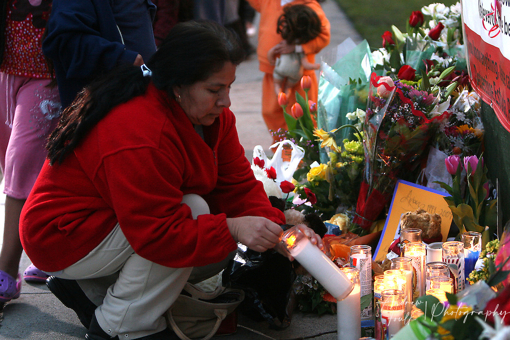 /Andrew Foulk/ For the North County Times/  .Maria Blancas, of Escondido, lights a candle before placing it near photo of  Amber Dubois during a Vigil to remember the fourteen year old at Escondido High School Monday night.
