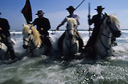 """Europe, France, Camargue, Saintes Maries de la Mer. Guardians on horseback in the surf during the procession. The Gypsy festival """"le Pelerinage des Gitans aux Saintes Maries de la Mer"""" takes place every year in mid May. Gypsies arrive from all over Europe a few weeks before the main festival days, the 24th and 25th May.  The pilgrimmage is Catholic but many Gypsies, Manouche, Gitans, Roma come to see their patron 'Saint Sara' and for the festival atmosphere, the yearly gathering of friends, the music and dance. Gypsies are still regarded with much distrust and racism, they are not liked by the shopkeepers but are well treated by the gentry, especially the Baroncelli family who were instrumental in making this officially a Gypsy festival. One Hundred years ago the Gypsies were not allowed into the church, as it is they still have to camp outside the town."""