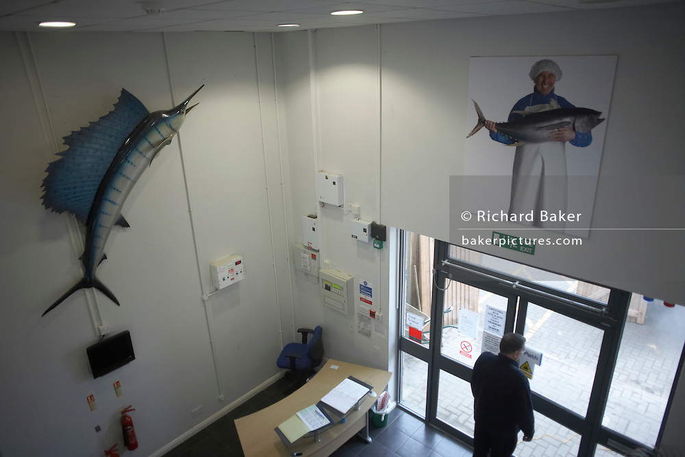 An employee of New England Seafoods, importers of fish products, leaves by the main entrance under a model sailfish