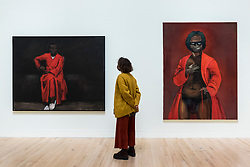 "© Licensed to London News Pictures. 02/12/2020. LONDON, UK. A staff member views (L to R) ""First"", 2003, and ""Any Number of Preoccupations"", 2010.  Preview of ""Lynette Yiadom-Boakye: Fly In League With The Night"" the first major UK survey exhibition by British artist Lynette Yiadom-Boakye.  Over 70 of her works spanning two decades are on display at Tate Britain.  It is the first new exhibition at Tate since the galleries were re-opened after coronavirus lockdown restrictions were slightly eased by the UK government.  Photo credit: Stephen Chung/LNP"