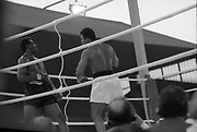 Ali vs Lewis Fight, Croke Park,Dublin.<br /> 1972.<br /> 19.07.1972.<br /> 07.19.1972.<br /> 19th July 1972.<br /> As part of his built up for a World Championship attempt against the current champion, 'Smokin' Joe Frazier,Muhammad Ali fought Al 'Blue' Lewis at Croke Park,Dublin,Ireland. Muhammad Ali won the fight with a TKO when the fight was stopped in the eleventh round.<br /> <br /> Image taken as Lewis is backed onto the ropes by the attacking Ali.