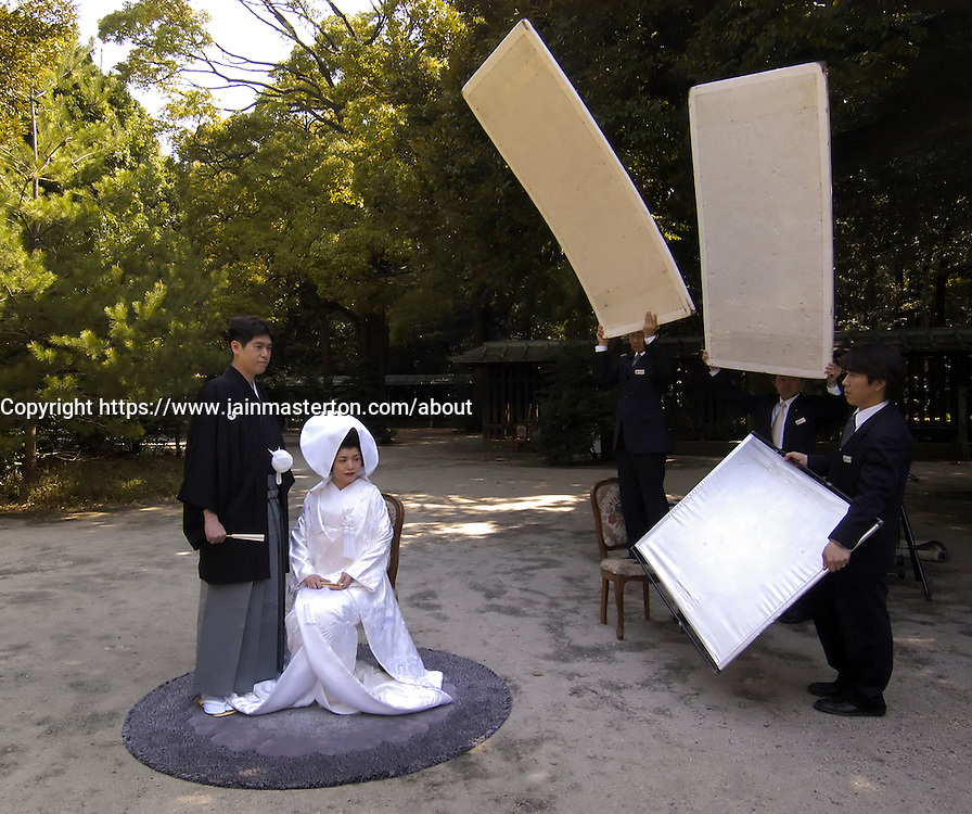 Wedding couple being photographed in grounds of famous Meiji Jingu Shrine in Tokyo