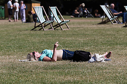 © Licensed to London News Pictures. 12/08/2016. LONDON, UK.  A woman sunbathes during the hot and sunny weather today in Green Park in London this lunchtime.  Photo credit: Vickie Flores/LNP