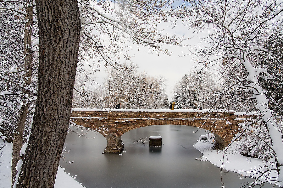 Students walk to class after a snowstorm on the University of Colorado campus in Boulder, Colorado. The brick bridge spans a frozen pond, an artificial lake used as a reservoir for campus irrigation.