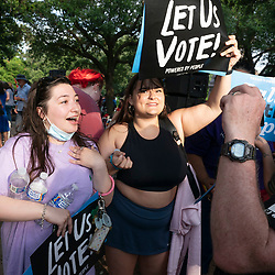 Two women yell at a man carrying an assault rifle on the Capitol grounds after a thousand Texas Democrats rally at the State Capitol supporting voting rights bills stalled in Congress and decrying Republican efforts to thwart voter registration and access to the polls.