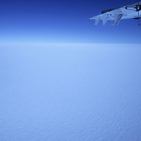 ANTARCTICA. Twin Otter airplane shadow crosses vast polar icecap near South Pole, featureless except for wind-carved sastrugi.