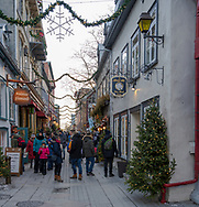 Quebec City, Quebec, Canada -- November 30, 2019.  Vertical photo of pedestrians doing some Christmas window shopping on a narrow street in Old Quebec.