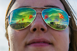 Flags in the field in front of the other stage. The 2015 Glastonbury Festival, Worthy Farm, Glastonbury.