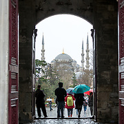 Visitors come and go in the rain through the Imperial Gate (Bâb-ı Hümâyûn) at Topkapi Palace, with tne entrance framing the Blue Mosque in the distance. On a peninsula overlooking both the Bosphorus Strait and the Golden Horn, Topkapi Palace was the primary residence of the Ottoman sultans for approximately 400 years (1465–1856) of their 624-year reign over Constantinople and the Ottoman Empire. Today it is one of Istanbul's primary tourist attractions.