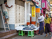 "06 NOVEMBER 2015 - YANGON, MYANMAR: A man buys knockoff designer sunglasses from a Yangon street vendor. Some economists think Myanmar's informal economy is larger than the formal economy. Many people are self employed in cash only businesses like street food, occasional labor and day work, selling betel, or working out of portable street stalls, doing things like luggage repair. Despite reforms in Myanmar and the expansion of the economy, most people live on the informal economy. During a press conference this week, Burmese opposition leader Aung San Suu Kyi said, ""a great majority of our people remain as poor as ever.""  PHOTO BY JACK KURTZ"