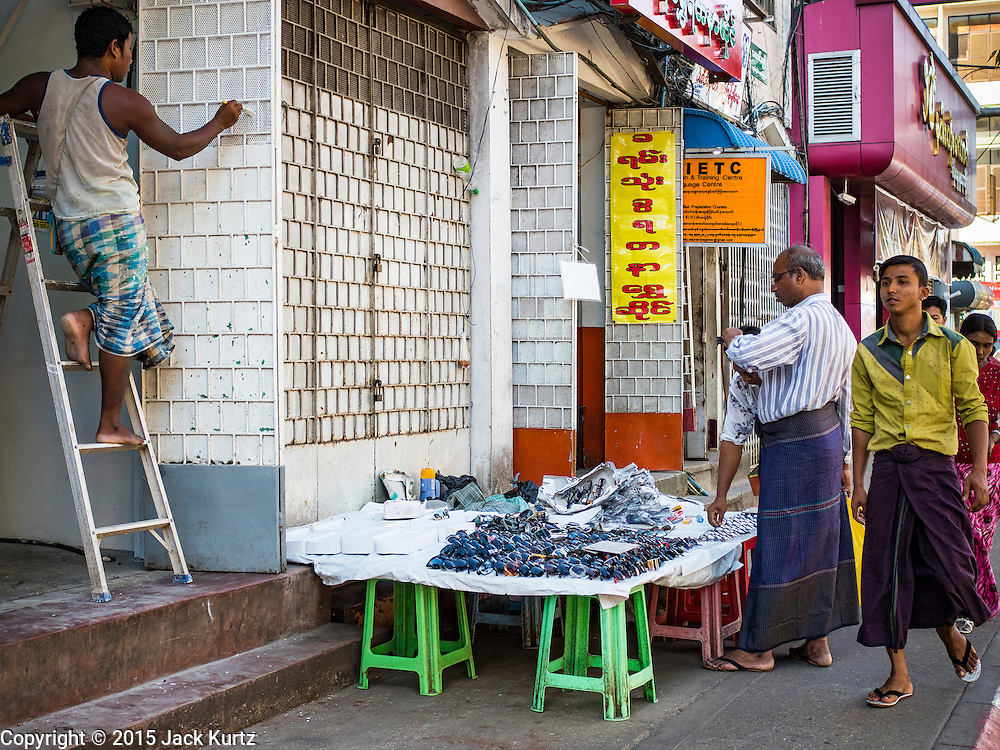 """06 NOVEMBER 2015 - YANGON, MYANMAR: A man buys knockoff designer sunglasses from a Yangon street vendor. Some economists think Myanmar's informal economy is larger than the formal economy. Many people are self employed in cash only businesses like street food, occasional labor and day work, selling betel, or working out of portable street stalls, doing things like luggage repair. Despite reforms in Myanmar and the expansion of the economy, most people live on the informal economy. During a press conference this week, Burmese opposition leader Aung San Suu Kyi said, """"a great majority of our people remain as poor as ever.""""  PHOTO BY JACK KURTZ"""
