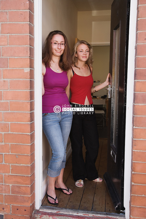 Two Polish students standing in their doorway of their home,