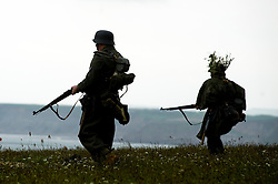 Members of the Northern World War Two Association portraying German soldiers of GrossDeutschland Division silhouetted against a light grey sky on the clifftops during a battle reenactment at Scarborough Castle Saturday 29th May 2010 .Images © Paul David Drabble.