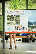 Low section of female hiker looking at the route map, Routeburn Shelter, South Island, New Zealand