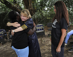 March 8, 2016 - Charlesville, Liberia - KATHLEEN CONLEE with HSUS gives a farewell hug to African caregivers as JENNY DESMOND (right) watches at a farewell party on March 8, 2016 given by LCR (Liberian Chimpanzee Rescue) a project of Humane Society of the United States, to save research chimpanzees abandoned by New York Blood Center in Liberia which stopped all funding for food and water when they retired the chimps formerly used for experimentation.  Humane Society of the United States and New York Blood Center came to an agreement recently in May 2017 after years of discussion about the care of research chimps. NYBC also refused to pay their original caregivers who had worked for the center and were abandoned as well.  The caregivers initially used their own meager finances to continue feeding them.  Over 60 chimps now live on six islands serving as a sanctuary run by Jenny and James Desmond to improve the dire situation in which the chimpanzees were left to die. (Credit Image: © Carol Guzy via ZUMA Wire)