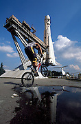 Teenager jumping water on BMX by VVC Exhibition centre and Soyuz Rocket, Moscow, Russia