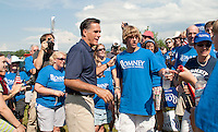 Mitt Romney and Drew Ingoldsby greet visitors along with the Romney crew as they entire Opechee Park following the July 4th parade Monday afternoon.   (Karen Bobotas/for the Laconia Daily Sun)