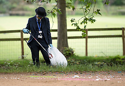 © Licensed to London News Pictures. 04/06/2021. Oxford, UK. A member of staff at Christ Church college, Oxford University cleans up in Christchurch Meadow after students celebrate finishing their final exams with the tradition known as 'trashing'. Oxford University is attempting to clamp down on the tradition which sees students throwing food, confetti and drink over their classmates. Photo credit: Ben Cawthra/LNP