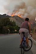 A bicyclist watches as a smoke plume from a brushfire rises in San Gabriel Canyon above Azusa, California, Monday, September 23, 2013.  A fire that began above Azusa burned north into the Angeles National Forest and was growing. The fire started at 5:56 p.m. and county firefighters fought the blaze with SuperScoopers, helicopters and ground forces. (Photo by Ringo Chiu/PHOTOFORMULA.com)