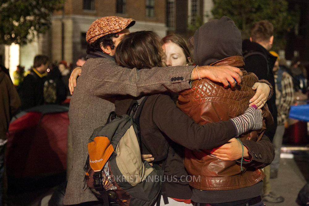 A group hug to keep warm and to keep up the spirit. The London Stock Exchange was attempted occypied in solidarity with Occupy Wall in Street in New York and in protest againts the economic climate, blamed by many on the banks. Police managed to keep people away fro the Patornoster Sqaure and the Stcok Exchange and thousands of protestors stayid in St. Paul's Square, outside St Paul's Cathedral. Many camped getting ready to spend the night in the square.