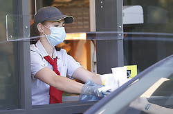 © Licensed to London News Pictures. 20/05/2020. Gillingham, UK. A customer is served as queues build up at a McDonald's Drive Through restaurant in Gillingham, Kent. A small number of Drive Through only branches are opening today. The government has announced a series of measures to slowly ease lockdown, which was introduced to fight the spread of the COVID-19 strain of coronavirus. Photo credit: Peter Macdiarmid/LNP