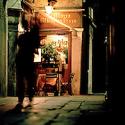 A person walking down a street, outside a local trattoria in Venice, Italy