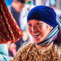 """Dong Van, Ha Giang Province - Vietnam. Market Hmong Ethnic Groups<br /> <br /> The markets in North Vietnam offer great cultural diversity. Flower Hmong, White Hmong, Black Hmong, Thay, Thai or Dzao are selling their stuff on different days of the week. There are even backward markets, those markets are held every week one day back, so if this week's market is scheduled for Sunday, next week the market will be on Saturday, then Friday…A row of ambulant barbers is placed on the sidewalk and take care of their customers while shoppers flock around in search of new trends, tribal clothes or just their weekly grocery. Most of those markets have one thing in common, ethnic teenagers are dressing up to attract the other gender, since the size of the small communes and distances in between makes it hard for them to find the """"right one"""". Nevertheless in most cases the parents choose the """"right one"""". There are cows, puppies or birds changing ownership. Some market ladies reminded me on witch doctors offering their alternative medicine such as indefinable roots, dried mushrooms, wood bark or certain parts of fluffy animals. There is 3-5 years old rice wine waiting in jerrycans for shoppers to try and buy. As a highlight for the fancy dressed White Hmong a lot stack of colorful cloth is waiting."""