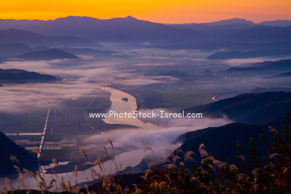 Misty morning sunrise over the bay and city of Toyooka (Toyooka-shi) is a city in the northern part of Hyogo Prefecture, Japan. The city was founded on April 1, 1950.