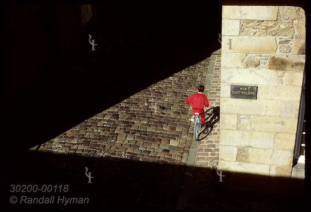 Overhead view of red-clad boy riding bike in patch of sunlight on stone street in Saint Malo. France