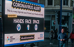 © Licensed to London News Pictures. 23/12/2020. London, UK. A man looks at a huge coronavirus alert sign warning members of the public to be vigilant in Putney, South West London as Health Secretary Matt Hancock announced in a televised address to the Nation this afternoon that yet another new Covid-19 mutation has been discovered in South Africa and is already in the UK as Downing Street orders many more areas of England to go into Tier 4. Tougher Covid-19 restrictions have already been implemented in London after the UK mutated strain continues to spread throughout the South East . Photo credit: Alex Lentati/LNP